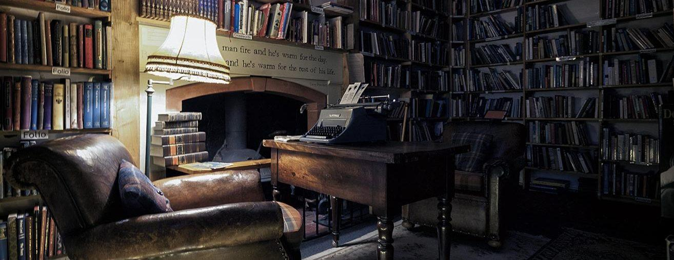 Interior of The Bookshop, Wigtown. Armchair by fireplace, bookshelves